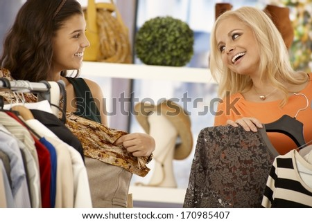Female friends shopping together at clothes store, smiling happy. - stock photo