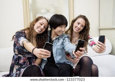Female friends taking self photograph - stock photo