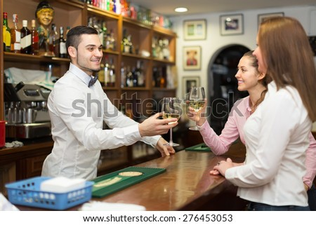 female friends 30 years old chatting and drinking wine in bar - stock photo
