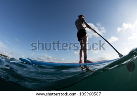 female from behind paddling a paddleboard on the ocean - stock photo