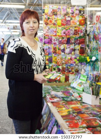 Female gardener buys the seeds on the market - stock photo
