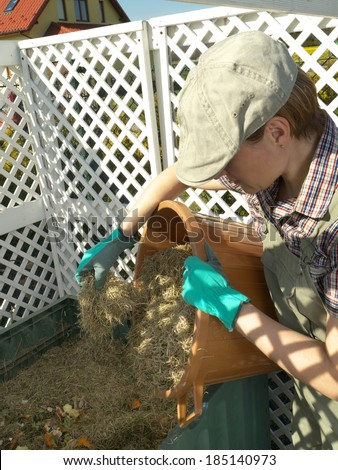 Female gardener dumping cut lawn grass into green plastic compost bin - stock photo