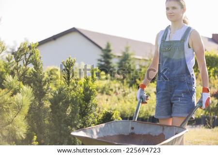 Female gardener pushing wheelbarrow at plant nursery - stock photo