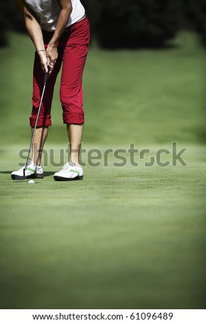Female golf player putting with ball just dropping into hole, with plenty of copy-space. - stock photo