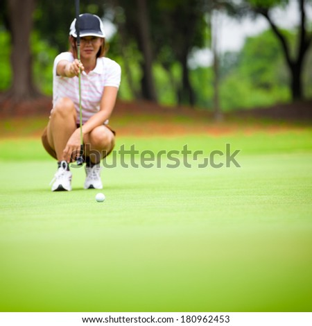 Female golf player with putter squatting to analyze the green at golf course, Select focus at golf ball - stock photo