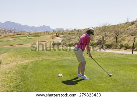 Female golfer at tee off concentrating on her shot - stock photo