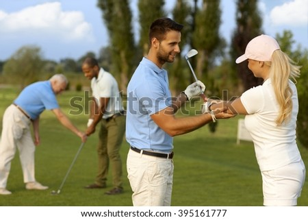 Female golfer learning golfing, male instructor helping. - stock photo