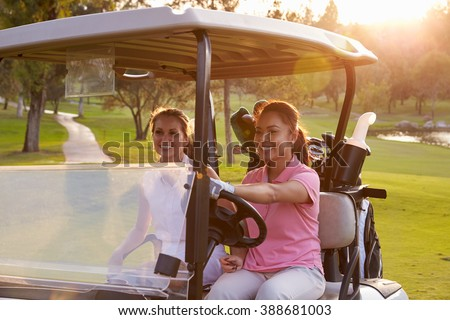 Female Golfers Driving Buggy Along Fairway Of Golf Course - stock photo