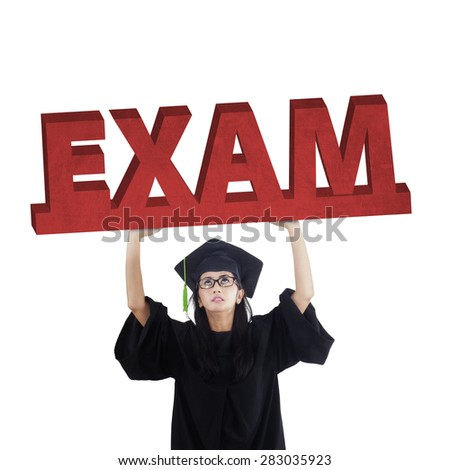 Female graduate student standing in the studio while holding an exam text, symbolizing an exam pressure - stock photo