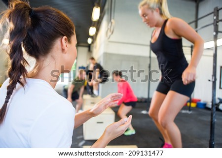 Female gym instructor encouraging athlete in box jumping at gym - stock photo