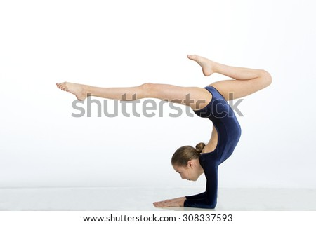 Female gymnast balancing in a pose on her arms against a white background. - stock photo
