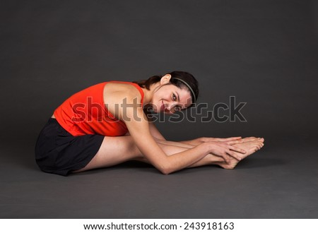 Female Gymnast in a red shirt and black shorts stretching and warming up - part of a series - stock photo