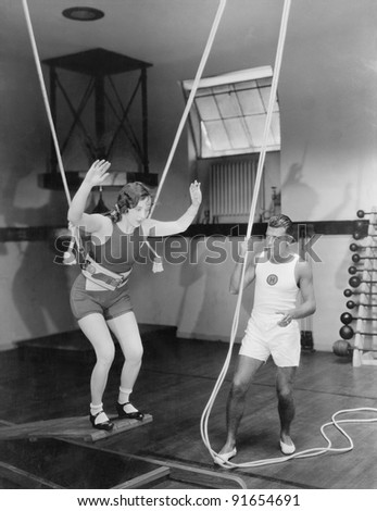 Female gymnast training with safety ropes with coach - stock photo