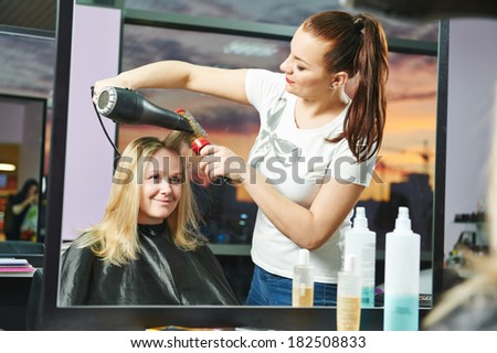 Female hairdresser drying hair with blow dryer of woman client at beauty parlour after highlighting - stock photo