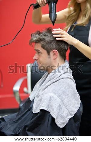 Female hairdresser drying her male customer's hair in her salon - stock photo