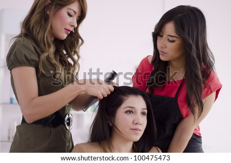 Female hairstylist teaching an apprentice - stock photo