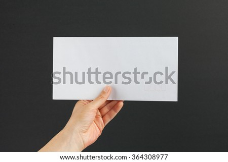Female hand delivering a white postage envelope on black background - stock photo