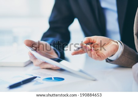 Female hand during explanation of report in touchpad - stock photo
