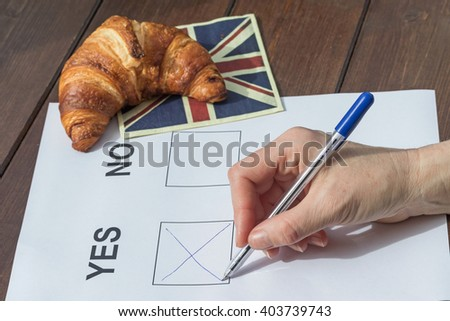 Female hand filled YES in the printed form. On the wooden table is lying a napkin English flag design, on which is symbolically lying a French croissant. - stock photo