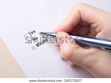 female hand filling survey with yes, no, maybe answers with pen - stock photo