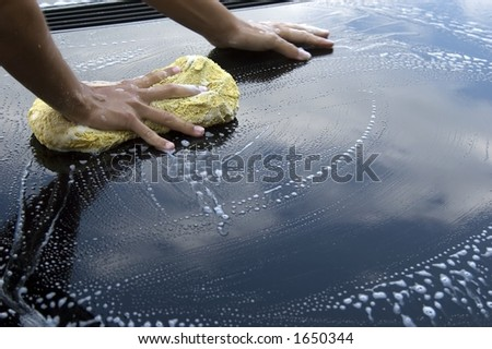 female hand giving car a sponge - stock photo