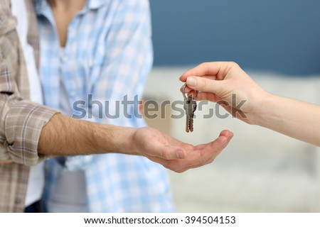 Female hand giving keys from new apartment to male hand on blurred background - stock photo