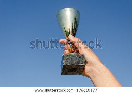 female hand hold award metallic cup on blue sky background  - stock photo
