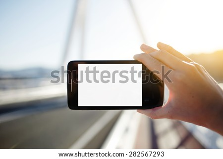 Female hand hold smart phone with blank copy space area for your text message or content,tourist woman holding cell phone while taking a photograph of landscape in summer travel,empty digital screen  - stock photo