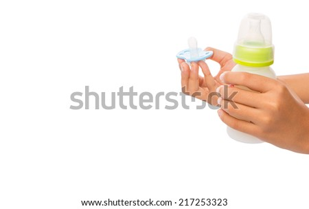 Female hand holding a bottle of baby's formula milk and blue pacifier over white background - stock photo