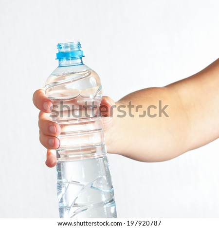 Female hand holding a bottle of fresh water - stock photo