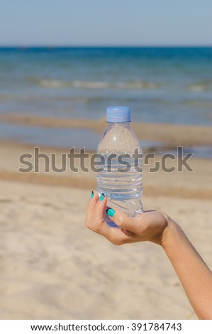 Female hand holding a bottle of water against beach background - stock photo
