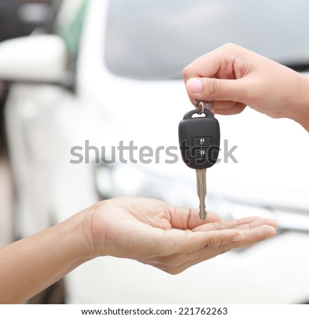 Female hand holding a car key and handing it over to another person isolated - stock photo