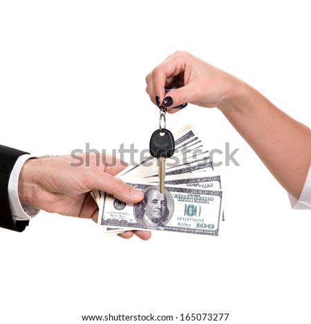 Female hand holding a car key and handing it over to another person.Man holding dollars. - stock photo