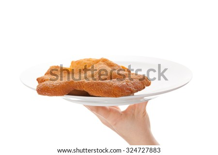 Female hand holding a plate with wiener schnitzel isolated on white background with reflection. Traditional european cuisine. - stock photo