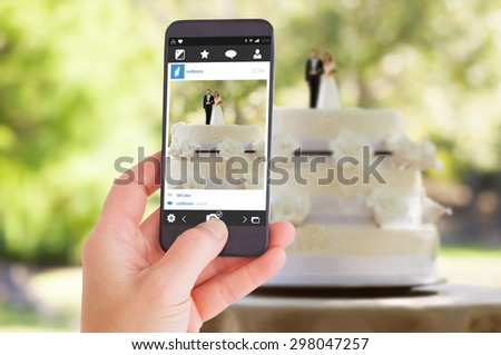 Female hand holding a smartphone against close-up of figurine couple on wedding cake - stock photo