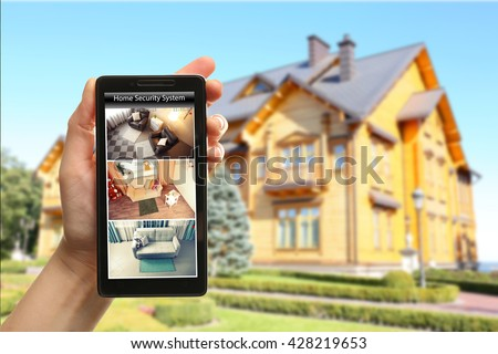 Female hand holding a smartphone on blurred house background. Home security system concept - stock photo