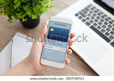 female hand holding a white phone with app mobile wallet on the screen on a table with laptop - stock photo