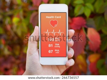 female hand holding a white phone with health card on a background of colored leaves  - stock photo