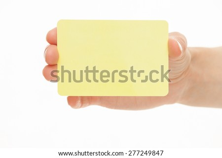 Female hand holding a yellow  paper card, white background - stock photo