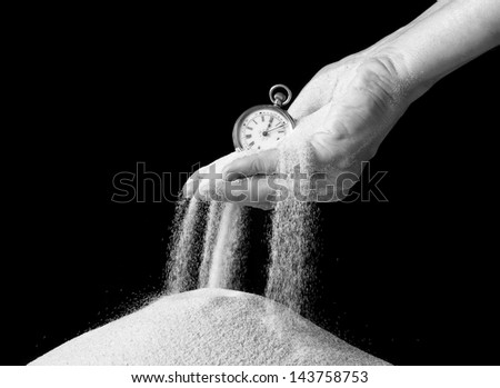 Female hand holding an antique pocket watch and sand flowing away - stock photo