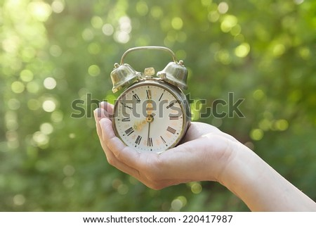 female hand holding and old clock alarm with natural green bokeh background, concept of freshness and waking up - stock photo
