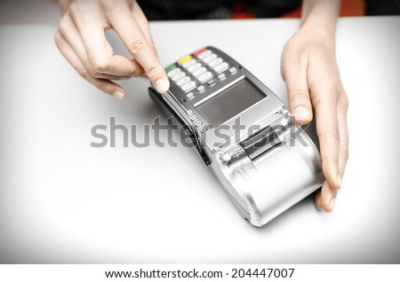 Female hand holding  bank terminal and plastic card  - stock photo
