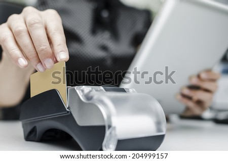 Female hand holding  bank terminal and tablet pc. Toned in high-tech style. - stock photo