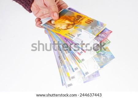 female hand holding banknotes Swiss franc - stock photo