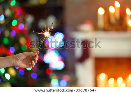 Female hand holding beautiful sparkler on Christmas background at home - stock photo