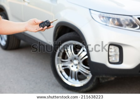 Female hand holding car key with suv on background - stock photo