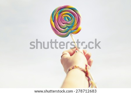 Female hand holding colorful spiral lollipop over sky / With copy space for your text - stock photo