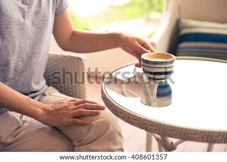Female hand holding cup of coffee in coffee shop - stock photo