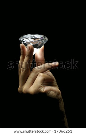 Female hand holding diamond - stock photo