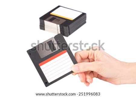 Female hand holding floppy disk on background of a stack of floppy disks - stock photo